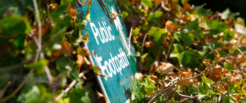 Nahaufnahme eines englischen Schildes, das den öffentlichen Wanderweg anzeigt